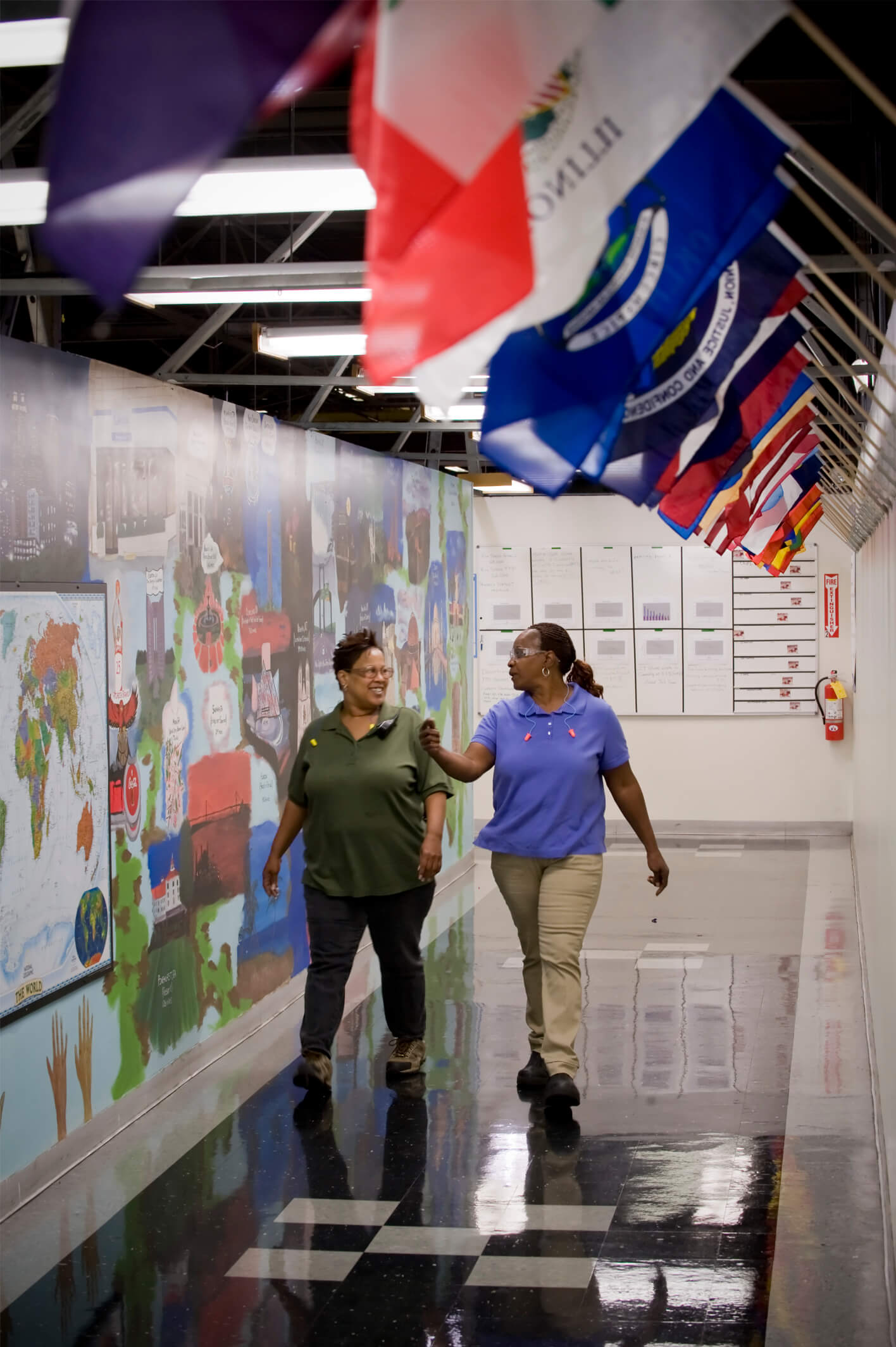Two women walking down a hallway with national flags hanging from the wall.
