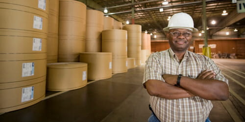 A man with his arms folded standing in front of paper rolls.