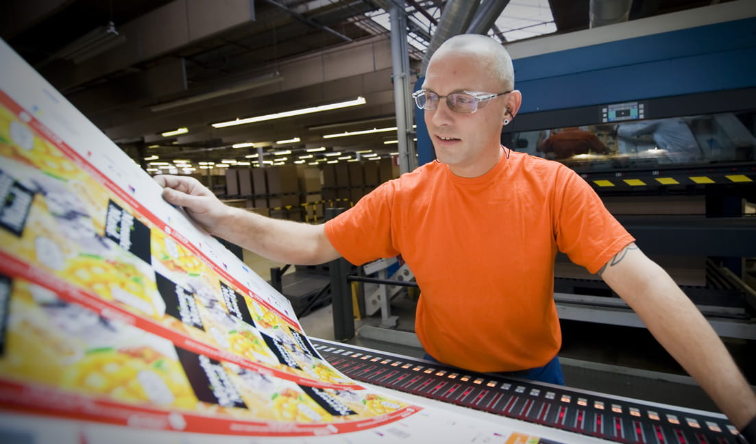 A man in orange shirt looking over commercial printing sheets at a manufacturing facility
